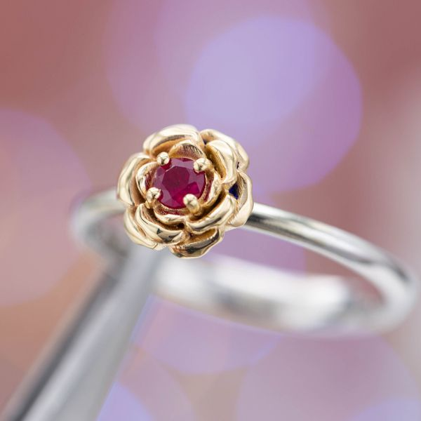 This ring sets a rose gold rose on a white gold band, a ruby nestled in the softly rounded petals.
