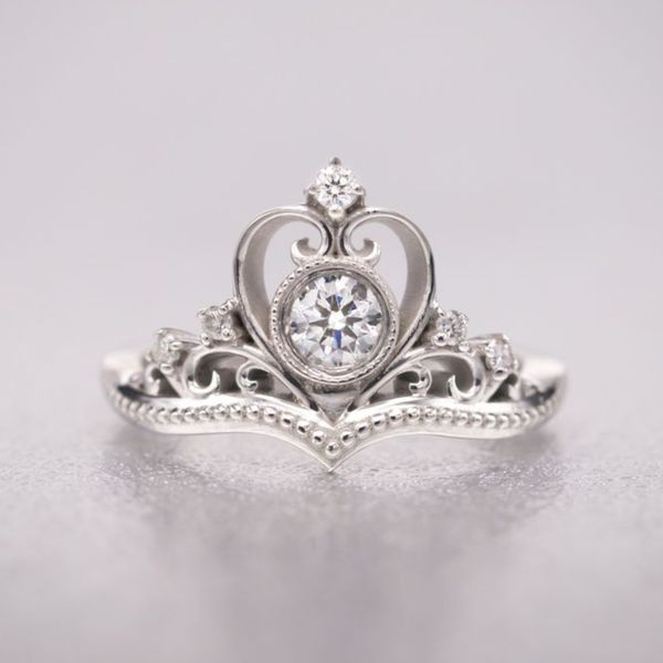 The perfect princess ring adds elegant scroll details and beadwork to this beautiful diamond tiara ring.