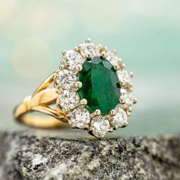 This emerald's deep, kelly green and characteristic fractures fit perfectly in the vintage-themed styling of the engagement ring we designed for it.