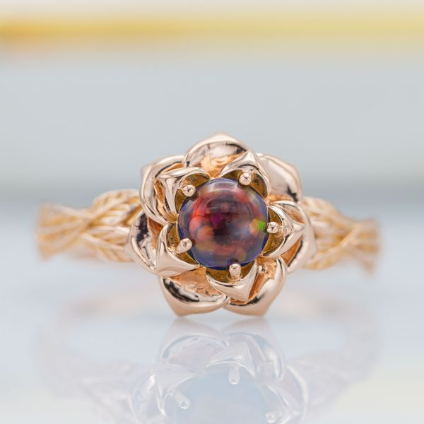 With its natural flower blossom setting, this black opal engagement ring uses five prongs, aligning organically with the petals.
