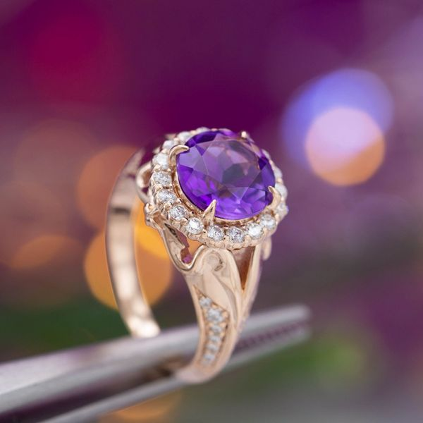 A halo of diamonds around a royal purple amethyst, all set on an elegant rose gold ring.