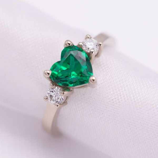 Three-stone setting of heart-cut emerald and round brilliant diamonds. Set in a clean, contemporary white gold band (in our hypoallergenic no-nickel palladium white gold alloy).