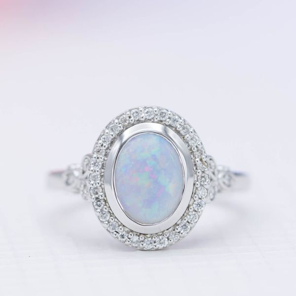 This opal ring uses a polished bezel to create the illusion of space between the opal and its diamond halo.