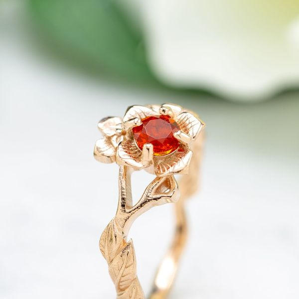 The intense orange of a fire opal makes the perfect center stone for this floral rose gold ring.