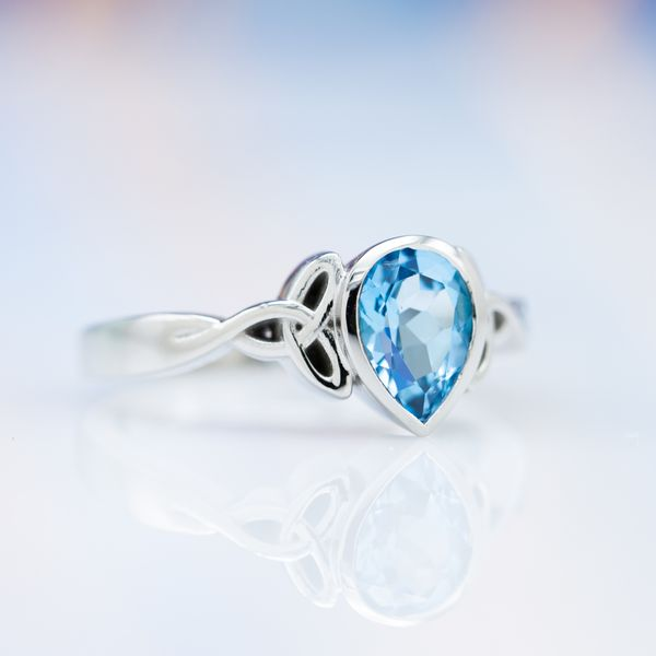 A simple, elegant design in 18k white gold with a pear cut Swiss blue topaz securely bezel set between trinity knots.