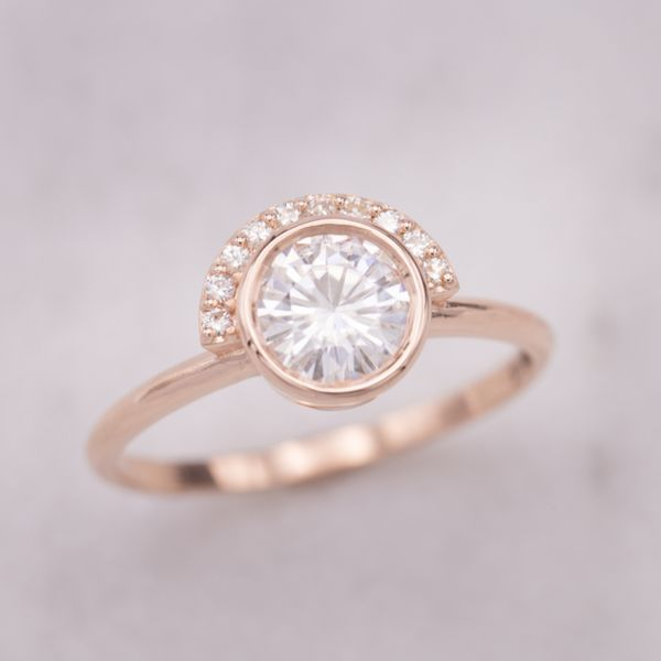 Delicate rose gold band with a modern half-halo wrapping around a large bezel set moissanite center stone.