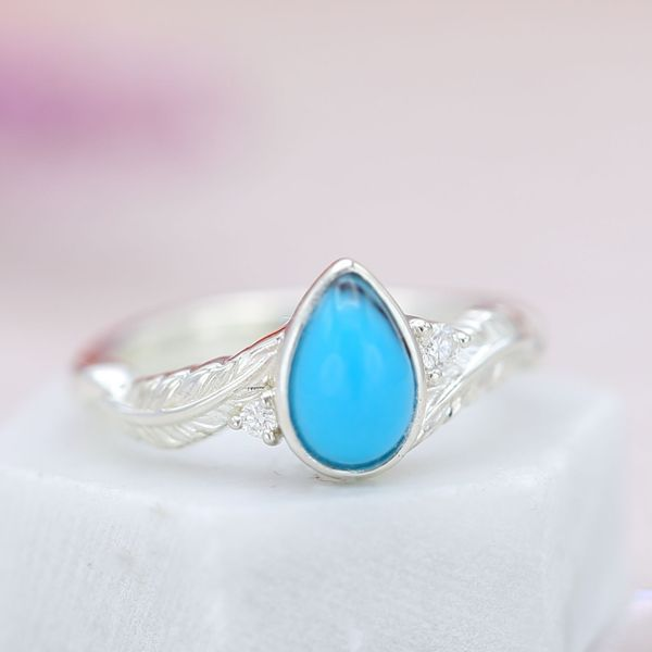 Feather engagement ring with a pear cut turquoise center stone and diamond accents.