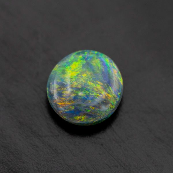 Black opal with intense green, yellow and orange color play.