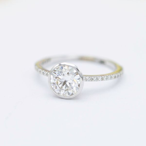 This delicate engagement ring uses a bezel setting for the center moissanite for a sleek, sparkly look.