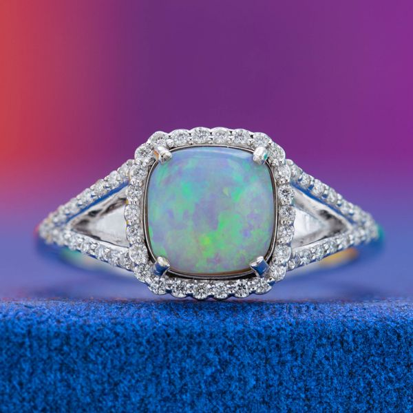 The start of this split shank engagement ring is an opal with shades of blue and green shimmering on its surface.