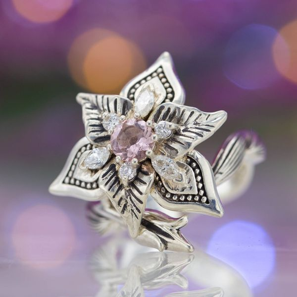 A bold, beautiful flower ring with a blossoming iris and vining bud tucked underneath. A pop of pink from the morganite center stone.