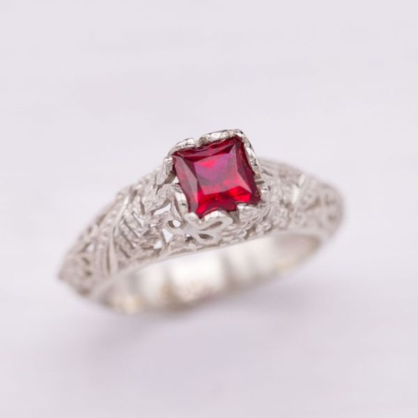 This bright red lab-created ruby nestles into a light, nature-inspired fern leaf and butterfly setting.