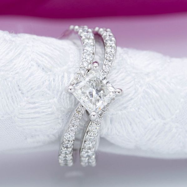 0.9ct princess cut diamond kite set on a tapered 14k white gold pave band. The engagement ring slots in to a bypass cuff wedding band to create the perfect bridal set.