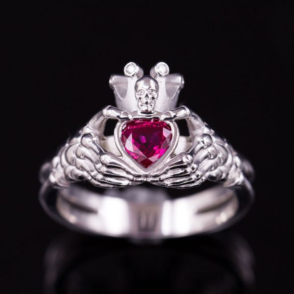 A play on the claddagh ring, with skeleton hands holding the heart and a skull on the crown.