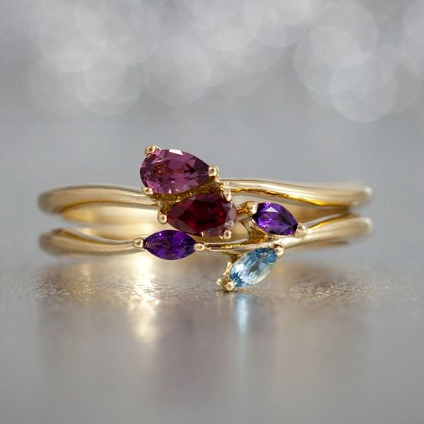 A surprise upgrade to her bridal set designed to reflect her family: nestled pear ruby and garnet reflect the couple, amethysts and aquamarine to incorporate their 3 kids.