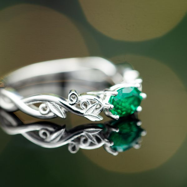 This delicate, white gold ring draws inspiration from nature and sets the oval emerald in a subtle east-west setting.