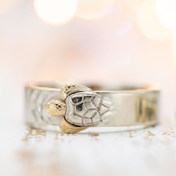A wide wedding band with a sculptural turtle rising from the surface of the metal.