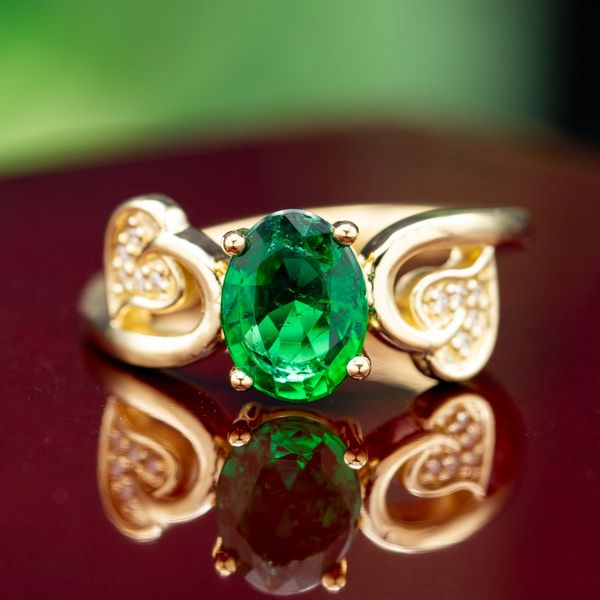 A clear, grass-green emerald is the perfect choice in this leafy, nature-inspired engagement ring.