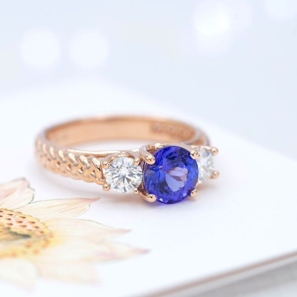 A perfect violet-tinted blue tanzanite center stone pairs with diamonds and braided rose gold in this engagement ring.