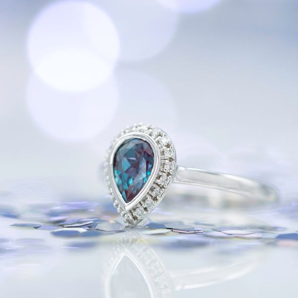 Lab-created alexandrite and diamond halo ring with a pear cut center stone.