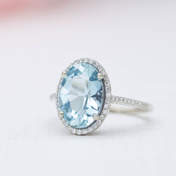A big, bright aquamarine center stone engagement ring with a thin halo of diamonds.
