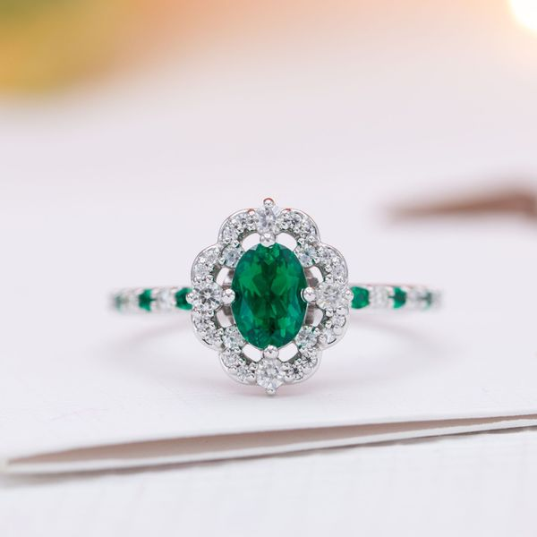 A floating, scalloped halo surrounds the emerald in this engagement ring.
