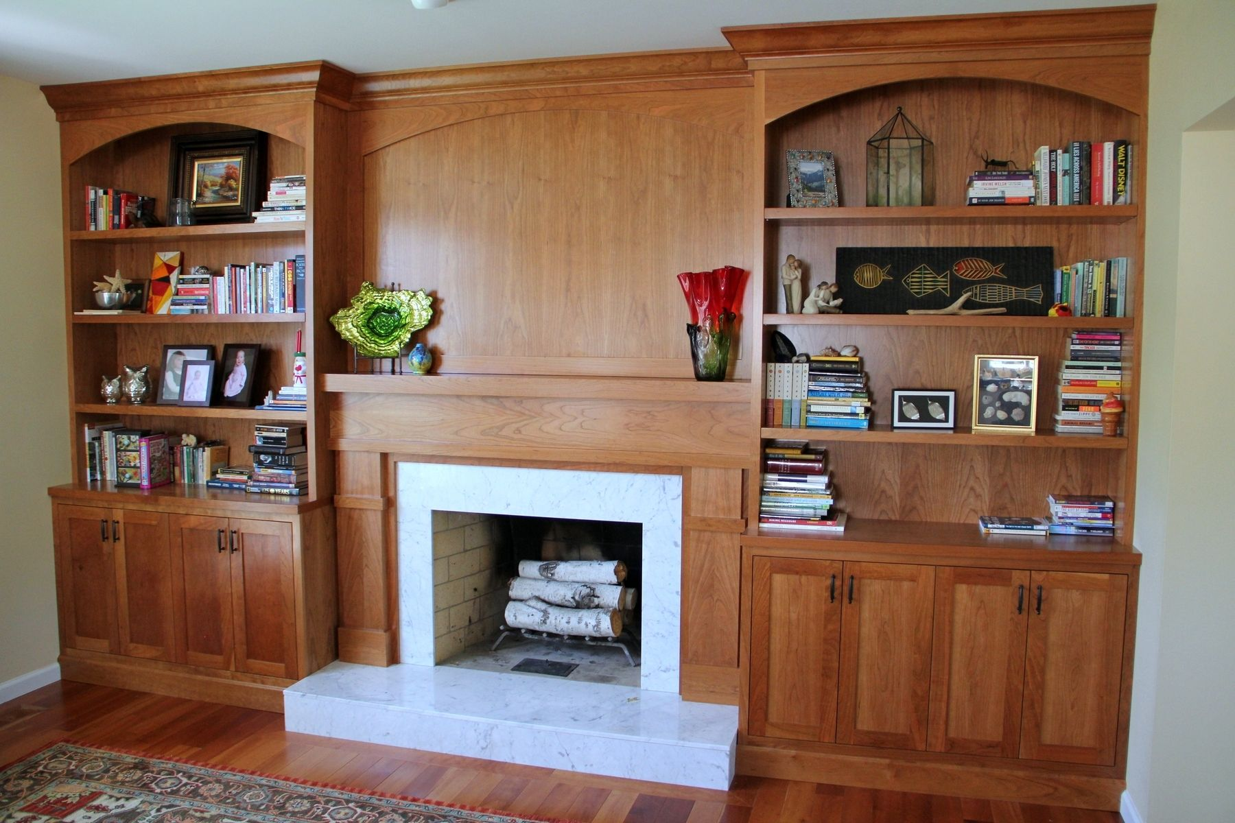 These built-in bookcases and fireplace surround replaced a simple fireplace mantle. The client chose to have these built-ins made form cherry wood. Th…