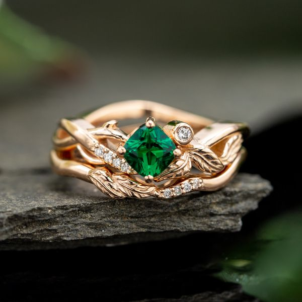 A delicate, nature-inspired bridal set with leaf and branch details in rose gold and a cushion cut, lab-created emerald.