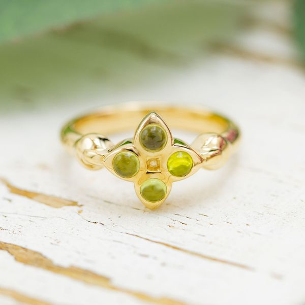 A unique cluster setting of 4 cabochon cut peridots in this game-inspired ring.