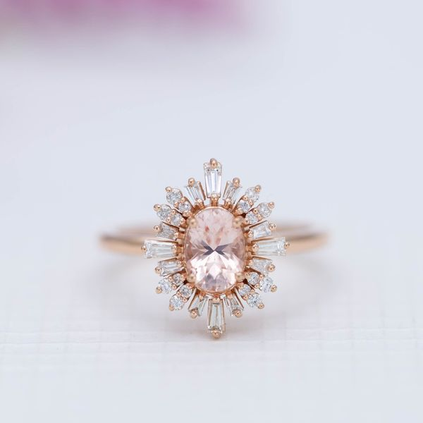 This morganite engagement ring surrounds the center stone with a bold, ballerina halo of baguette diamonds.
