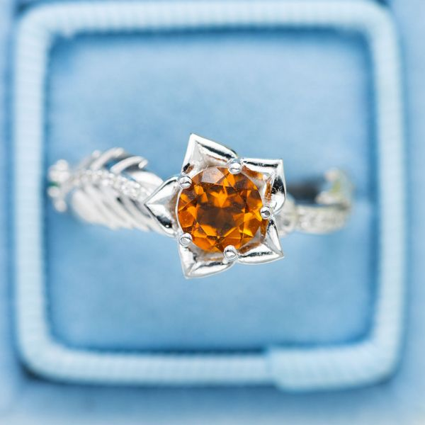 This flower engagement ring features a bright pop of yellow-orange citrine.