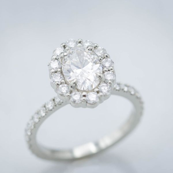 1.01ct oval diamond in a scalloped diamond halo and pave 18k white gold shank.