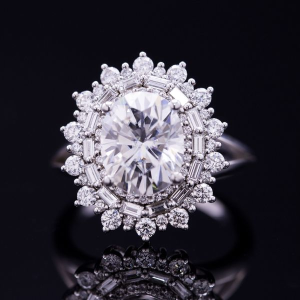 Stunning sunburst halo engagement ring with dozens of baguette and around diamonds surrounding an oval moissanite, which might one day be replaced by a diamond of the same size.