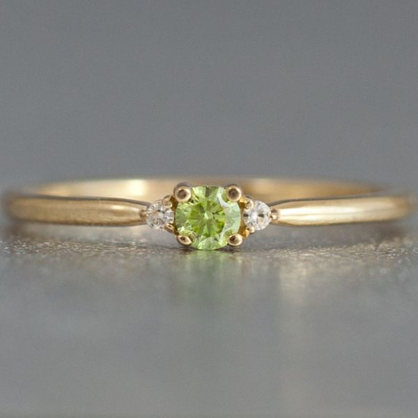 A fancy, apple green diamond in an ultra-delicate three-stone setting for a unique take on the popular, modern styling.