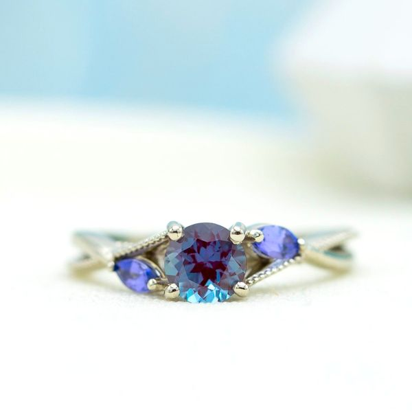 Two violet tanzanite accents in this delicate engagement ring will draw out the blue-purple hues from the alexandrite center stone in some lighting.