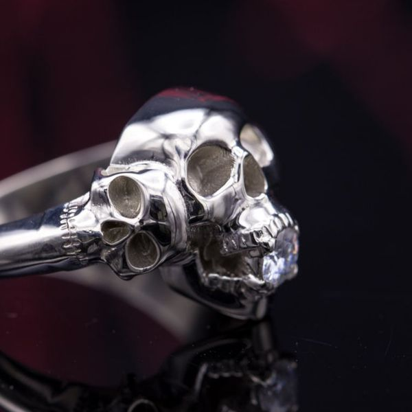 This one's at once morbid and a bit funny, the intense center skull gripping a diamond in its teeth.