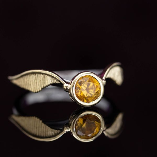 A Harry Potter fan's golden snitch engagement ring with a deep orange-yellow sapphire center stone.