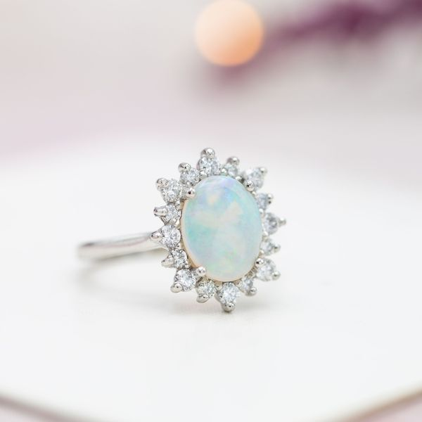 A sunburst halo creates the look of a snowflake around the cool blues and greens of this ring's opal center stone.