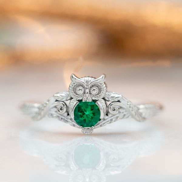 Owl engagement ring in white gold with an emerald center stone and feather detailing on the band.