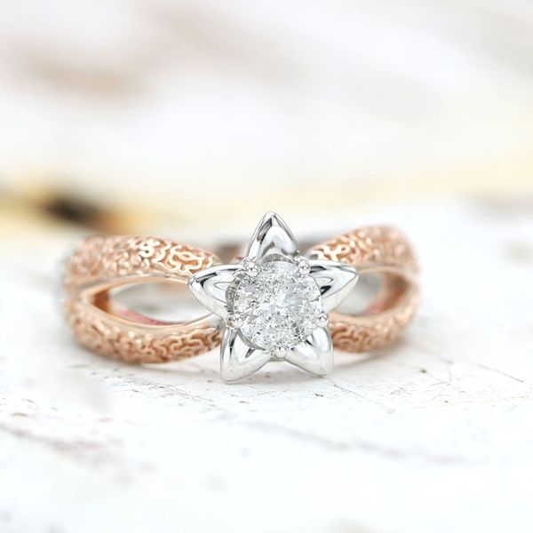 This whimsical setting blends rose and white gold, intricate detailing that almost becomes a textured surface, and a bright, sparkly, speckled salt and pepper diamond center stone.