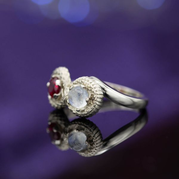 A two-stone ouroboros ring depicts a snake eating its own tail, winding an infinity symbol around a moonstone and a ruby.
