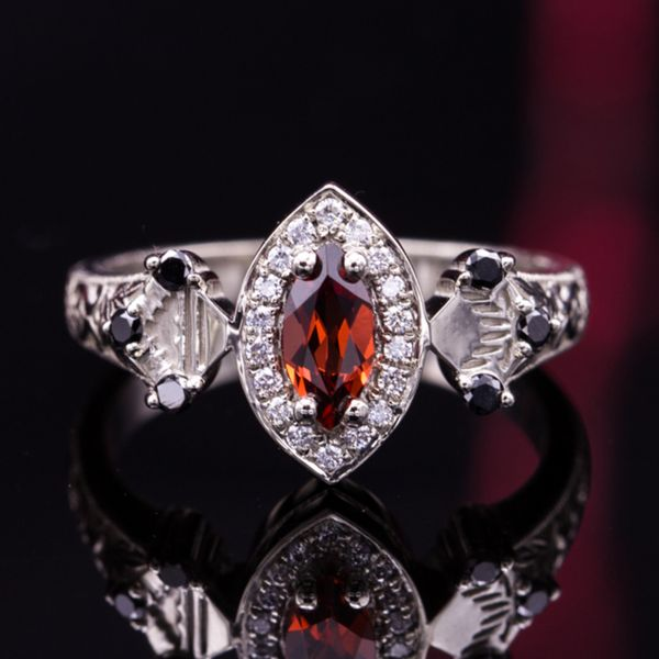 An intricate, vintage-inspired design in 14K white gold with an orange-red marquise garnet, diamond halo, and small black diamond accents on the shank.