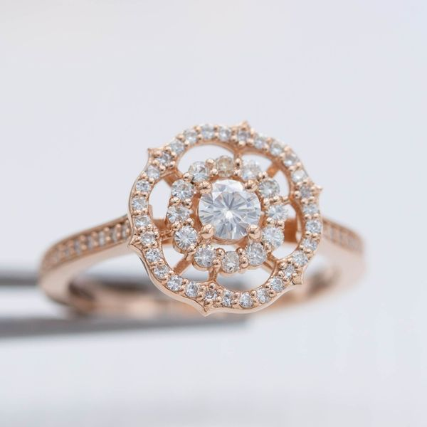 A snowflake-like ring balances a scalloped halo and antique frame halo and lots of open space to create a unique, balanced ring design.