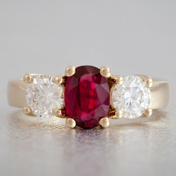 Classic gold 3-stone engagement ring with a deep red oval ruby flanked by round diamonds.