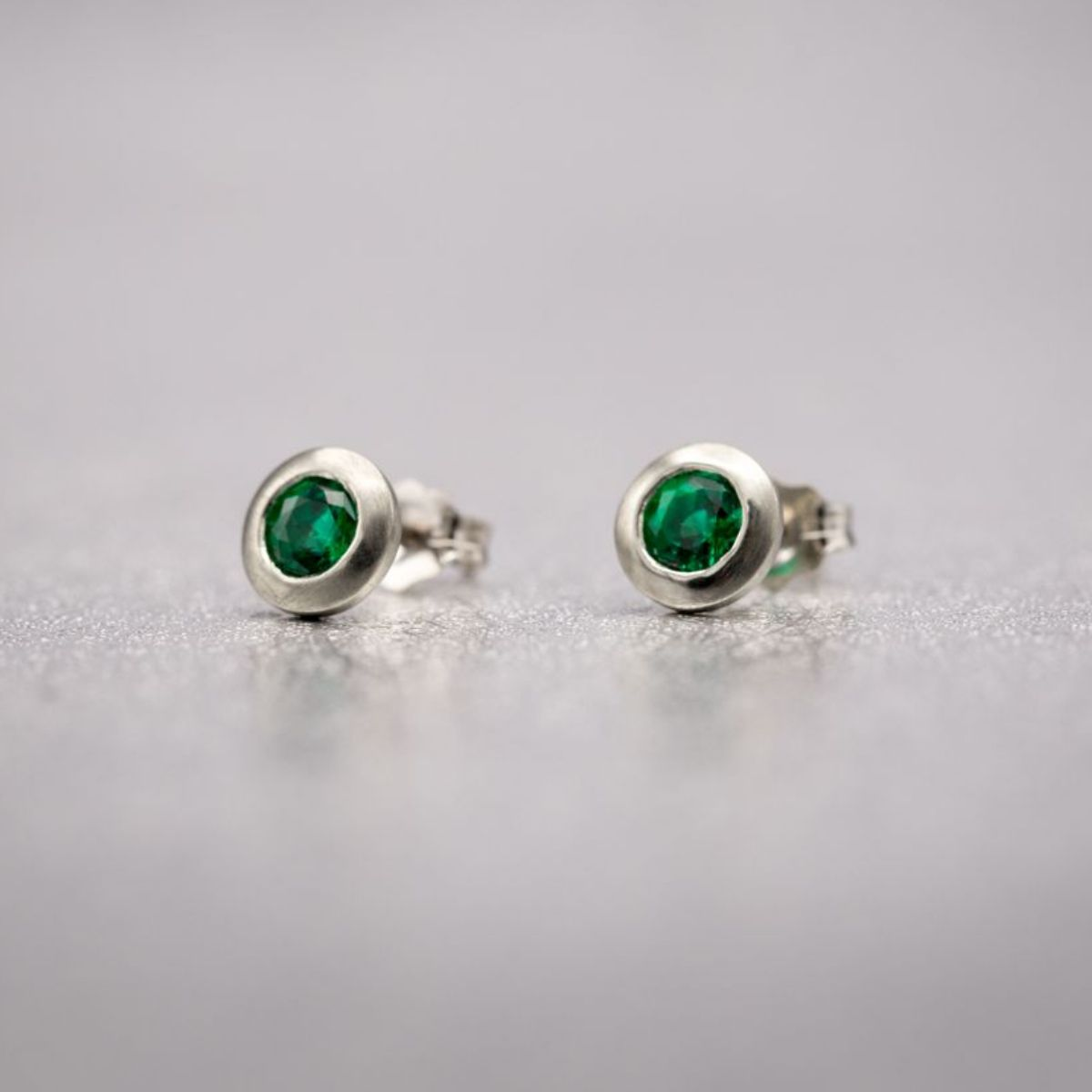 White Gold Studs With Bezel Set Emeralds And A Lightly Brushed Finish