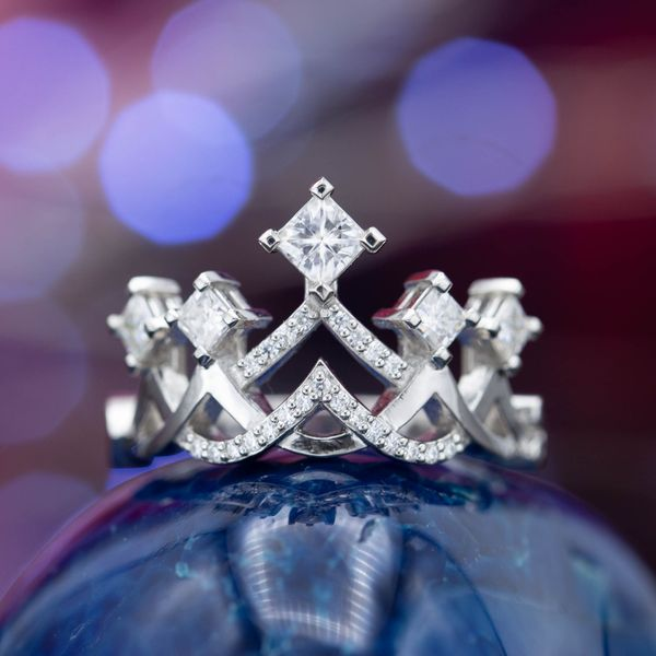 A crown ring with princess cut diamonds as the focal peaks and accent diamonds along the curves.