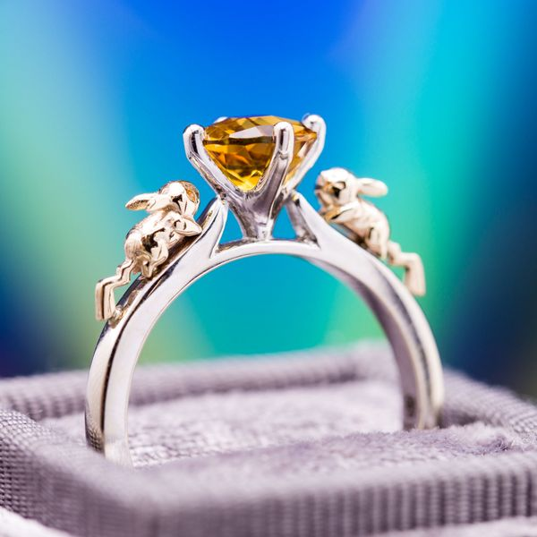 A Pokemon fan's wonderfully whimsical concept features yellow gold Pikachus dashing up the white gold engagement ring shank toward a bright orange citrine center stone.