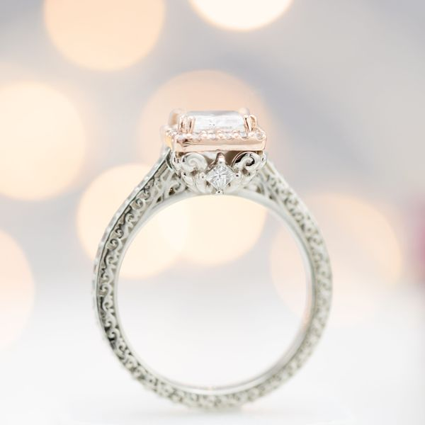 A small, princess cut peek-a-boo gem is tucked on the side of this engagement ring's center setting.