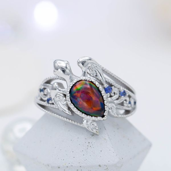 A pear cut black opal set as the shell of this turtle engagement ring with a guitar string-inspired band.