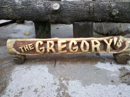 Hand made chainsaw carved name log through style by the